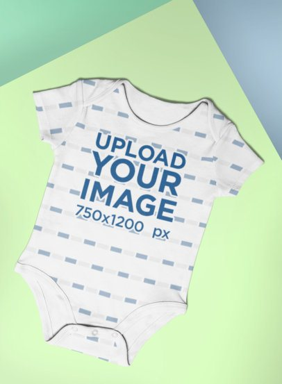Mockup of a Baby Onesie Lying in a Colored Setting 25177