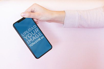 Mockup of a Girl Holding an iPhone XS by the Upper Corner 25437