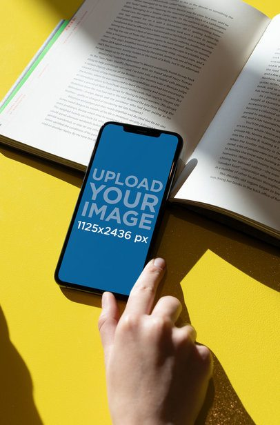 iPhone XS Mockup over an Open Book 25442