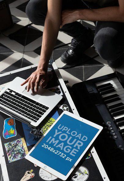 iPad Pro Mockup Featuring a Man Checking His Laptop at His Home Studio 25745