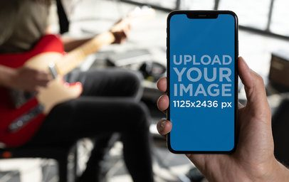iPhone XS Mockup Featuring a Man Playing Guitar in a Home Studio 25751