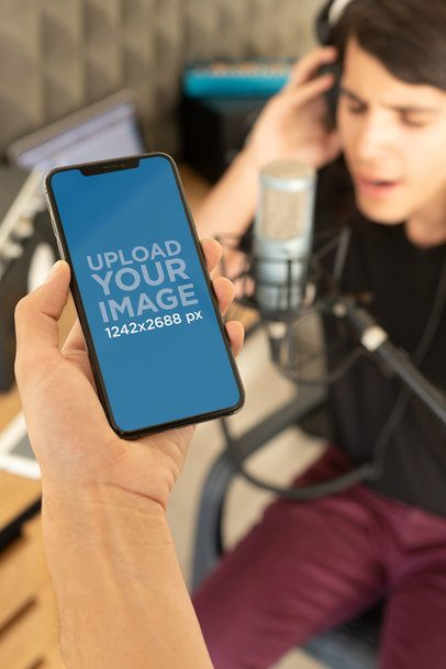 iPhone XS Max Mockup Featuring a Man Recording at a Home Studio 25756