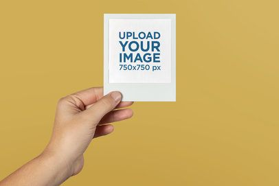 Mockup of a Hand Holding a Polaroid Picture Frame Against a Solid Surface 26172
