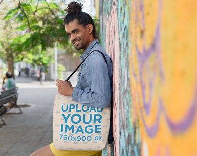 Tote Bag Mockup of a Man with a Hairbun Standing By a Colorful Wall 26708