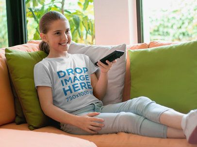 T-Shirt Mockup of a Young Girl Watching TV at Home a7926