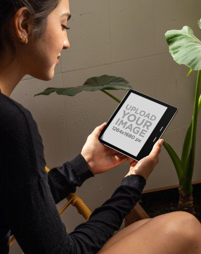 Kindle Oasis Mockup of a Woman Sitting Next to a Plant 26146