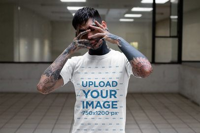 T-Shirt Mockup of a Tattooed Man Covering His Face in a Room 26601