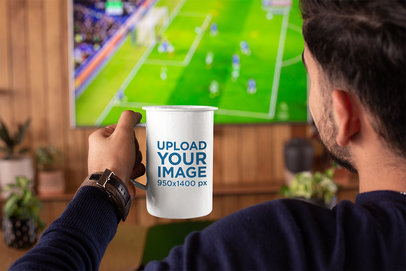 Mockup of a Man Watching a Soccer Match with a 21 oz Enamel Mug in His Hand 26939a