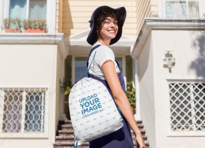 Drawstring Bag Mockup Featuring a Stylish Woman Standing  in Front of a House 27582