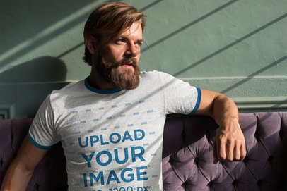 Ringer T-Shirt Mockup Featuring a Cool Bearded Man Sitting on a Purple Couch 27931