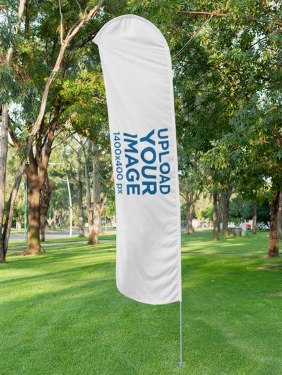 Mockup of a Flag Banner on a Grassy Area with Trees in the Background 28016