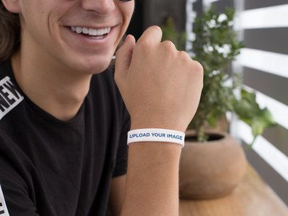 Silicone Wristband Mockup Featuring a Smiling Guy by a Plant Pot 28244