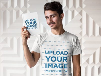 Tee Mockup of a Man Holding a Book Against a White Background 28500