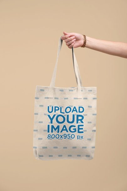 Tote Bag Mockup Being Held by a Hand Against a Flat Surface 28830