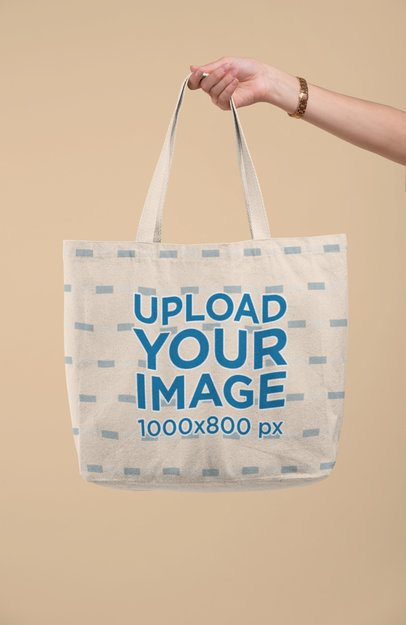 Mockup of a Hand Holding a Tote Bag Against a Solid Color Background 28835