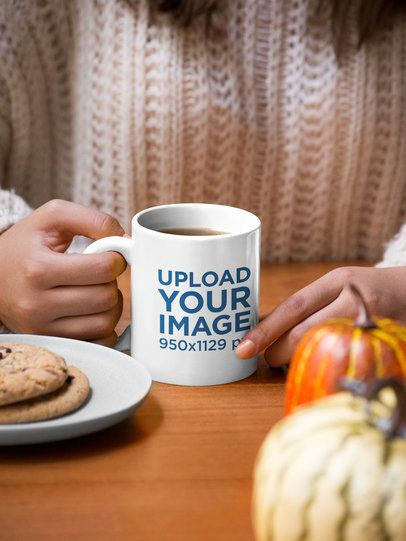 Mockup of a Woman Holding an 11 oz Mug with Cookies and Pumpkins at the Table 29136