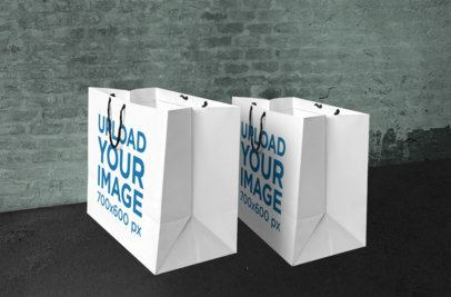 Mockup of Two Paper Shopping Bags in Front of a Brick Wall 658-el