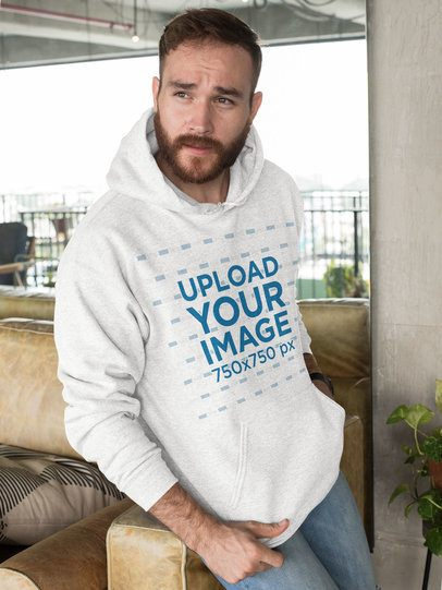 Pullover Hoodie Mockup Featuring a Bearded Man Leaning over a Sofa  28741