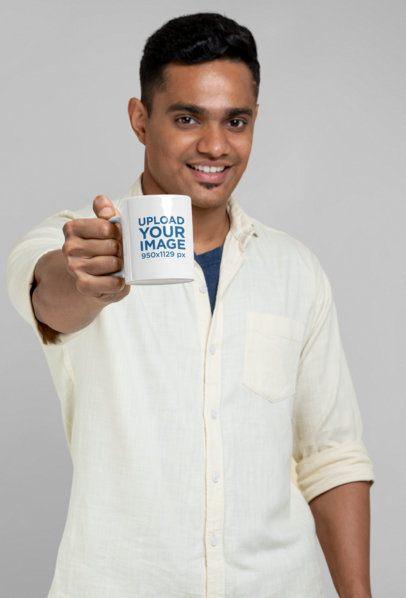 Mockup of a Man Showing an 11 oz Mug at a Studio 28962