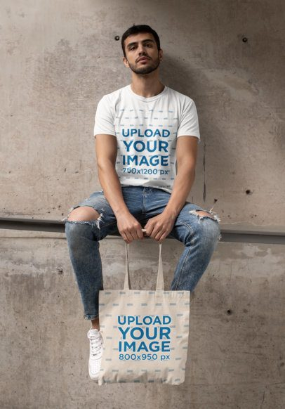 T-Shirt Mockup of a Bearded Man with a Tote Bag Sitting on a Concrete Structure 29412
