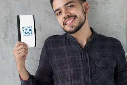 Mockup of a Man Holding an iPhone 8 Plus Wallet Case Against a Concrete Wall 29828