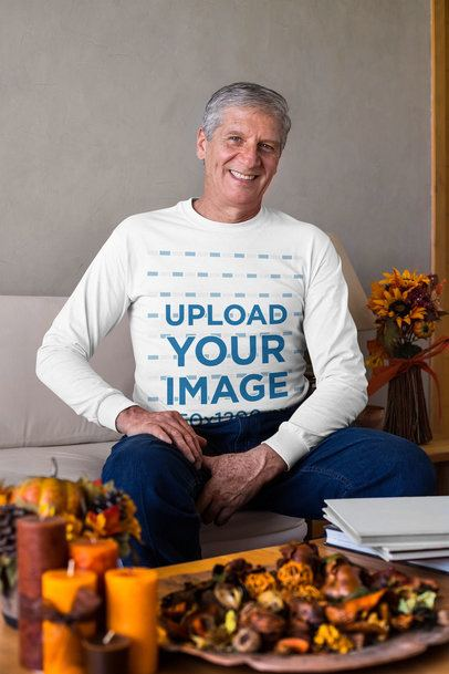 Long Sleeve Tee Mockup of a Senior Man Sitting at a Living Room with Thanksgiving Decorations 29929