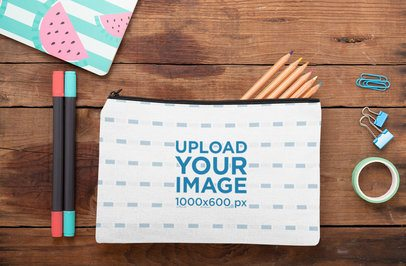 Mockup of a Pouch Laying on a Wooden Surface with Stationery Tools 29989