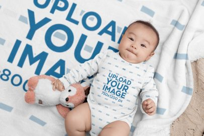 Mockup of a Baby Wearing a Onesie Lying on a Blanket 30048