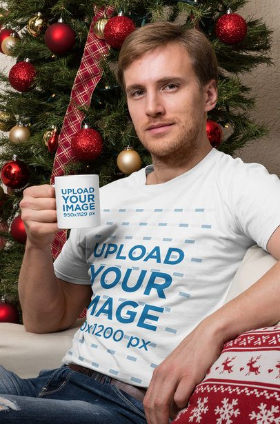 T-Shirt Mockup of a Man Holding an 11 oz Mug Sitting in Front of a Christmas Tree 30204