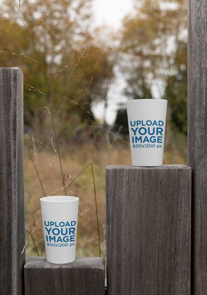 Mockup of Two Reusable Cups Placed on a Wooden Fence 30566