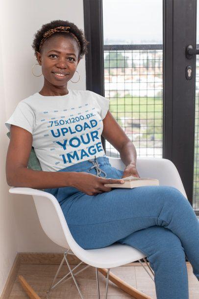 T-Shirt Mockup of a Smiling Woman Sitting at Home 30335