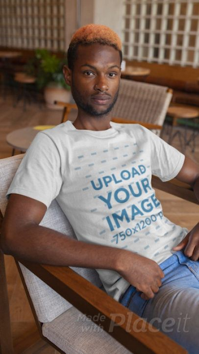 T-Shirt Video of a Young Man Sitting on a Modern Chair 22538