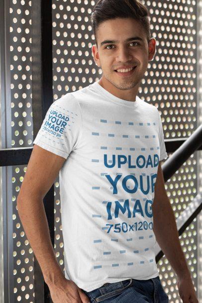 T-Shirt Mockup of a Man Posing Against a Metal Wall 30875