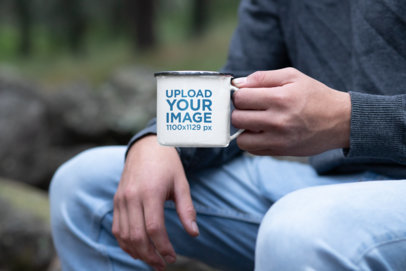 Mockup of a Man Holding a 12 oz Silver Rim Enamel Mug in the Forest 30821a