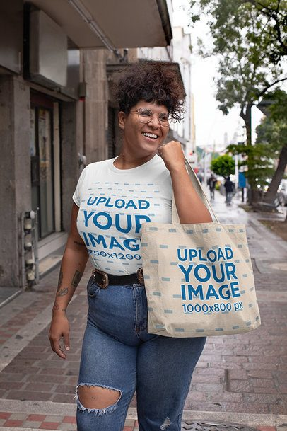 Plus Size T-Shirt Mockup of a Woman with Tattoos Holding a Tote Bag on the Street 30890