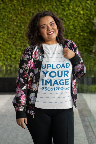 Plus Size T-Shirt Mockup Featuring a Joyful Woman Posing in Front of a Leafy Background 31077