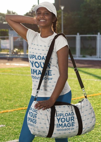 T-Shirt Mockup Featuring a Sporty Woman with a Duffle Bag at a Soccer Field 31352