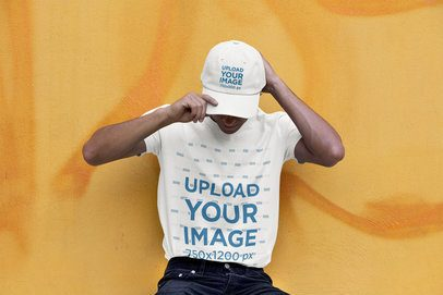 Tee Mockup Featuring a Man with a Dad Hat Leaning Against a Yellow Wall 31171