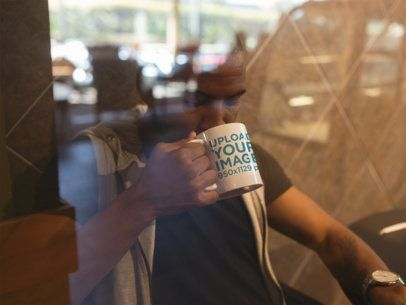 Young Black Man at a Coffee Shop Drinking from His Mug Mockup a12300