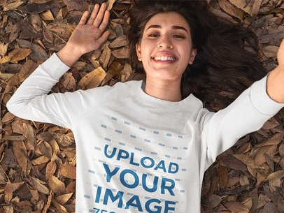 Crewneck Sweatshirt Mockup of a Woman Taking a Selfie While Lying on Some Autumn Leaves 31811
