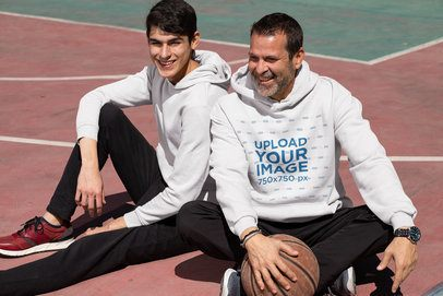 Hoodie Mockup Featuring a Man and His Son Chilling at a Basketball Court 33090
