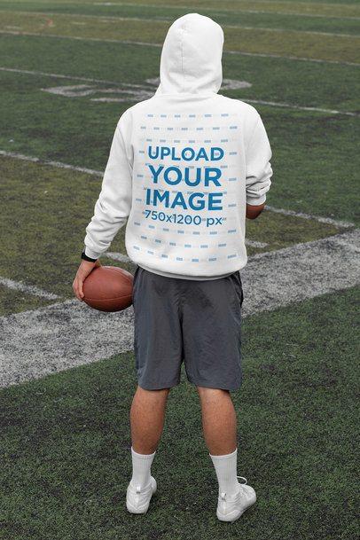Hoodie Mockup of a Man Facing Towards a Football Field 32500