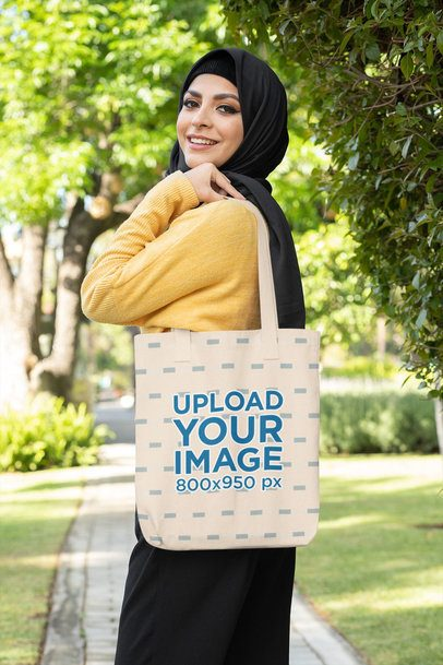 Mockup of a Smiling Woman in a Hijab Holding a Tote Bag 32409