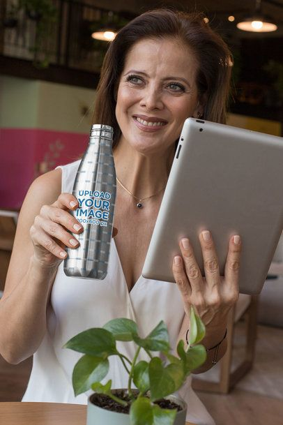 Mockup of a Woman Drinking From an Aluminum Bottle While Using a Tablet 33481
