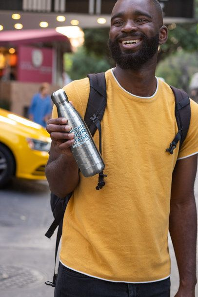 Mockup Featuring a Happy Man Holding a Sublimated Aluminum Bottle Outside 33523