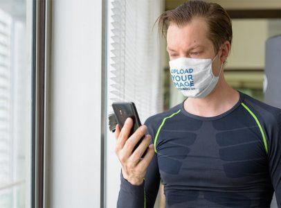 Face Mask Mockup of a Man Checking His Phone at the Gym 40348-r-el2