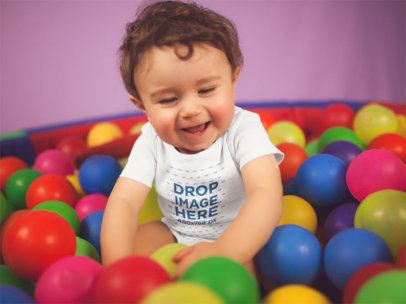 White Baby Boy Wearing a Onesie Smiling While Playing In The Ball Pit Mockup 14026
