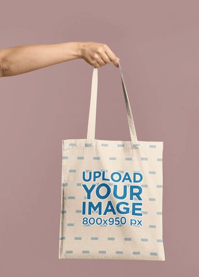 Mockup of an Arm Holding a Tote Bag In Front of a Colored Backdrop 41541-r-el2