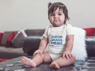 Mockup of a Sad Baby Girl Wearing a Onesie Sitting on a Leather Couch a14049