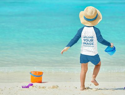 Mockup Featuring a Boy with a Raglan Long-Sleeve Tee Playing at the Beach 42115-r-el2